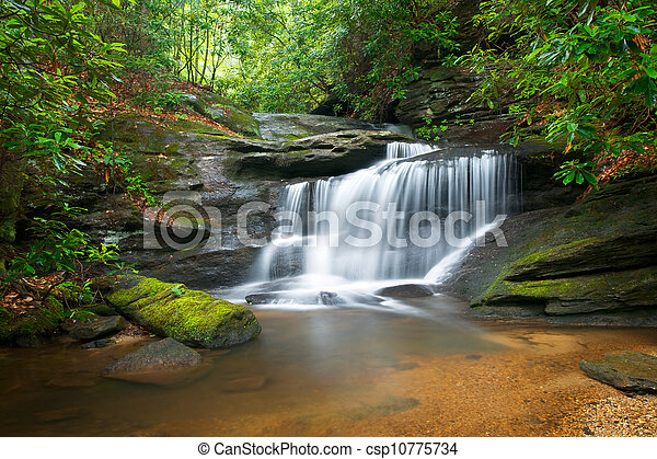Motion Blur Waterfalls Peaceful Nature Landscape in Blue Ridge Mountains with lush green trees, rocks and flowing water - csp10775734